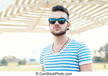Handsome hipster man with beard in sunglasses on a sunny day at the beach.