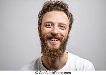 Handsome hipster man with beard smiling at camera over white background.