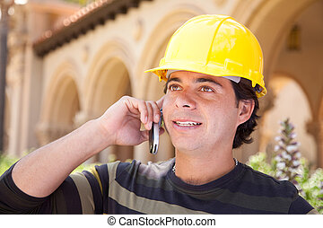 Handsome Hispanic Contractor on Phone with Hard Hat Outside