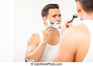 Handsome Hispanic man shaving his beard