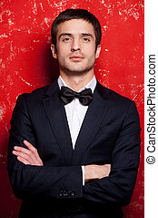 Handsome in bow tie. Handsome young man in suit and bow tie keeping arms crossed and looking at camera while standing against red background