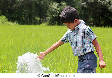 Handsome indian kid playing with water spring in a lush cultivated paddy field located in coastal karnataka of south india. The boy is aged around 6 years