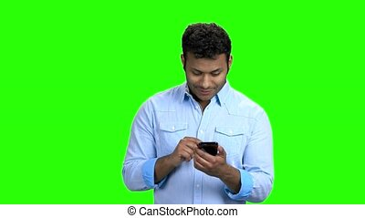 Handsome Indian man using phone on green screen. Young...
