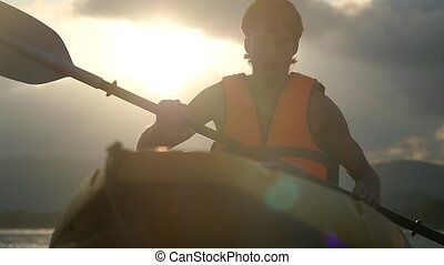 Handsome kayaker paddling at beautiful sunset and water...