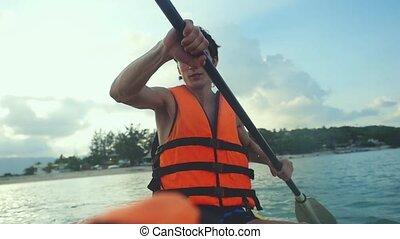 Handsome kayaker paddling at beautiful sunset and water...