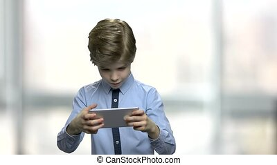 Handsome kid addicted to his cell phone. Handsome little boy...