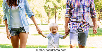 Handsome little boy having a walk with parents in the park