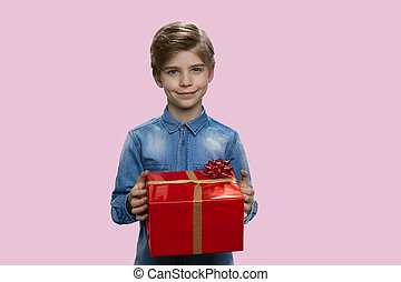 Handsome little boy holding red gift box.