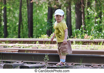 Handsome little boy in shorts stands on old railway at summer day