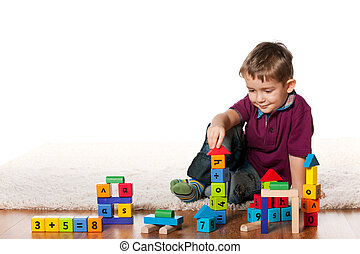 Handsome little boy on the floor with toys