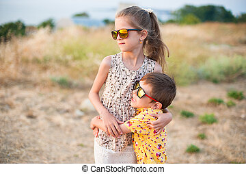 handsome little girl and boy wearing sunglasses hugging in field in summer