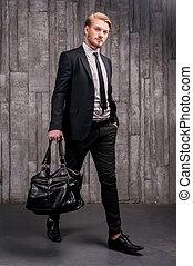 handsome., lleno, joven, formalwear, bolsa, longitud, proceso de llevar, negro, elegante, guapo, hombre