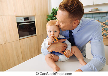 Handsome loving father kissing his baby daughter