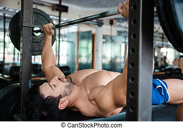 Handsome male bodybuilder doing bench press - Portrait of a ...