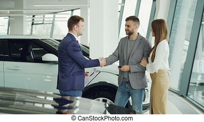 Handsome male car buyer is getting key fob from friendly salesman and shaking hands with him then kissing and hugging his attractive girlfriend while standing beside auto.
