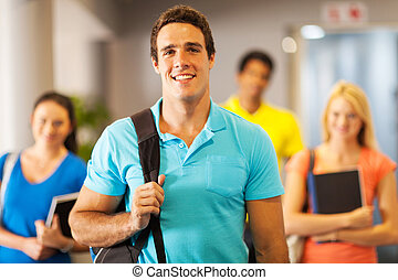 male college student standing in front of friends - handsome...