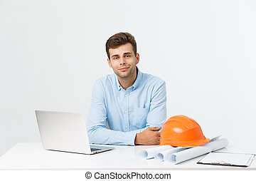 Handsome male construction engineer working in the office with laptop