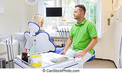 Handsome male dentist listening to his patient sitting in dentist chair