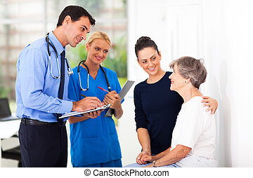 male doctor writing medical prescription for senior patient