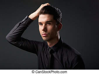Handsome male fashion model with hand in hair