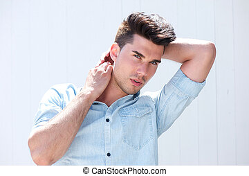 Handsome male fashion model with hands in hair