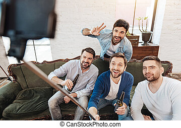 Handsome male friends looking into the smartphone camera