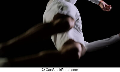 Handsome male gymnast in white clothes on a black background...
