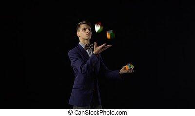 Handsome male in suit is juggling Rubik's Cube in dark. -...