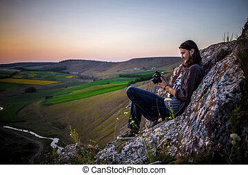 Handsome male model sitting on the rocks.