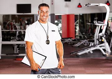 handsome male personal trainer in gym
