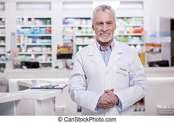 Handsome male pharmacist greeting in drugstore