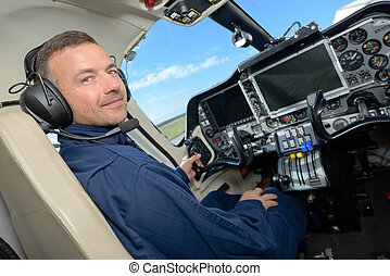 handsome male pilot in the cockpit