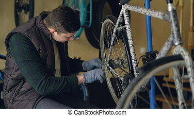 Handsome male serviceman in gloves is repairing back wheel...