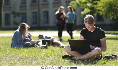 Handsome male student studying with laptop in park