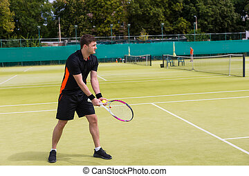 Handsome male tennis player getting ready to serve on a court outdoor