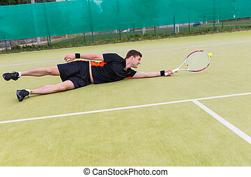 Handsome male tennis player in action during the game fallen on a court