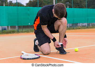 Handsome male tennis player tying shoelaces wearing a sportswear left racket and ball on a clay court