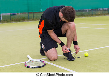 Handsome male tennis player tying shoelaces wearing a sportswear left racket and ball on a green grass court