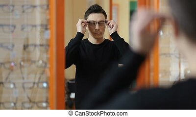 Handsome male trying eyeglasses in optical shop