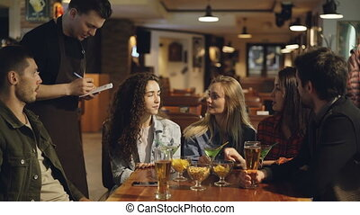 Handsome male waiter is coming to group of friends sitting at table in cafe and taking order. Young people are talking and laughing, waiter is very friendly and helpful.