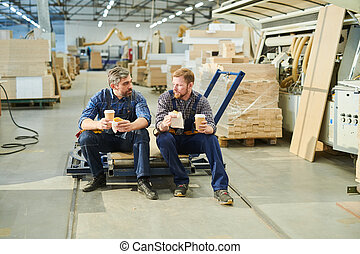Handsome male workers in uniform chatting at break