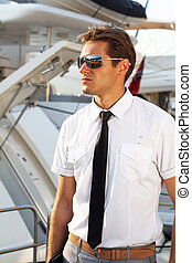Handsome man, a serious captain in a white shirt near the yacht, looking away