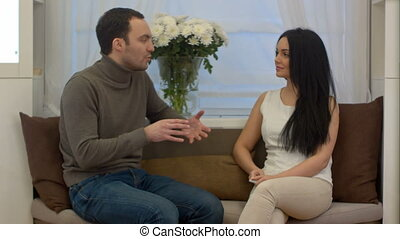 Handsome man and attractive brunette talking while sitting on sofa in their living room