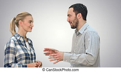 Handsome man and attractive young woman talking and smiling on white background.