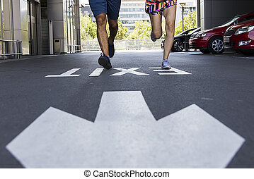 Handsome man and beautiful woman jogging together on street with exit sign
