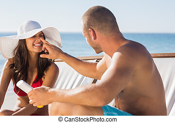 Handsome man applying sun cream on his girlfriends nose