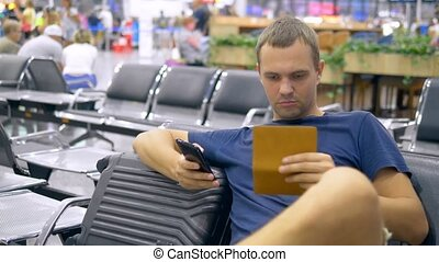 handsome man at the airport in the waiting room. man sits uses a smartphone and holds a passport with luggage.