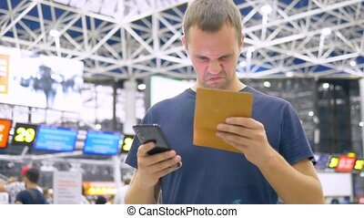 handsome man at the airport in the waiting room. man uses a smartphone and holds a passport