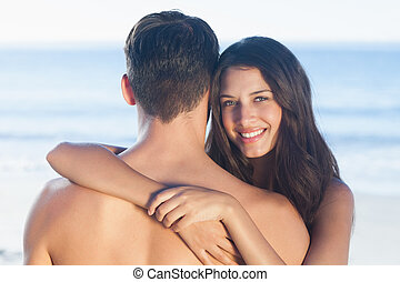 Handsome man being hugged by his girlfriend on the beach
