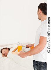 Handsome man bringing breakfast looking at his sleeping wife